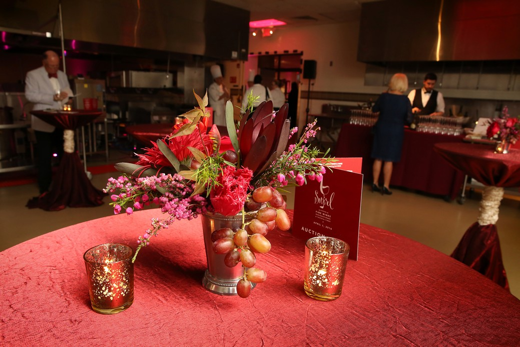 Floral and fruit centerpiece with votive candles on red table cloth