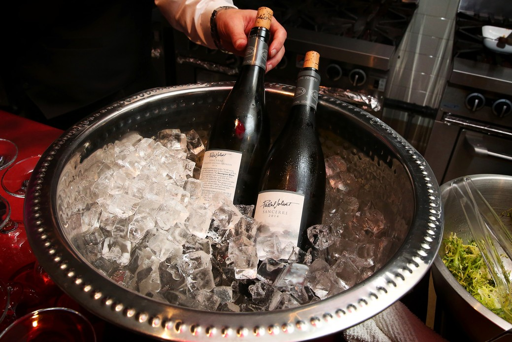 Two bottles of wine chilling in stainless steel bowl of ice