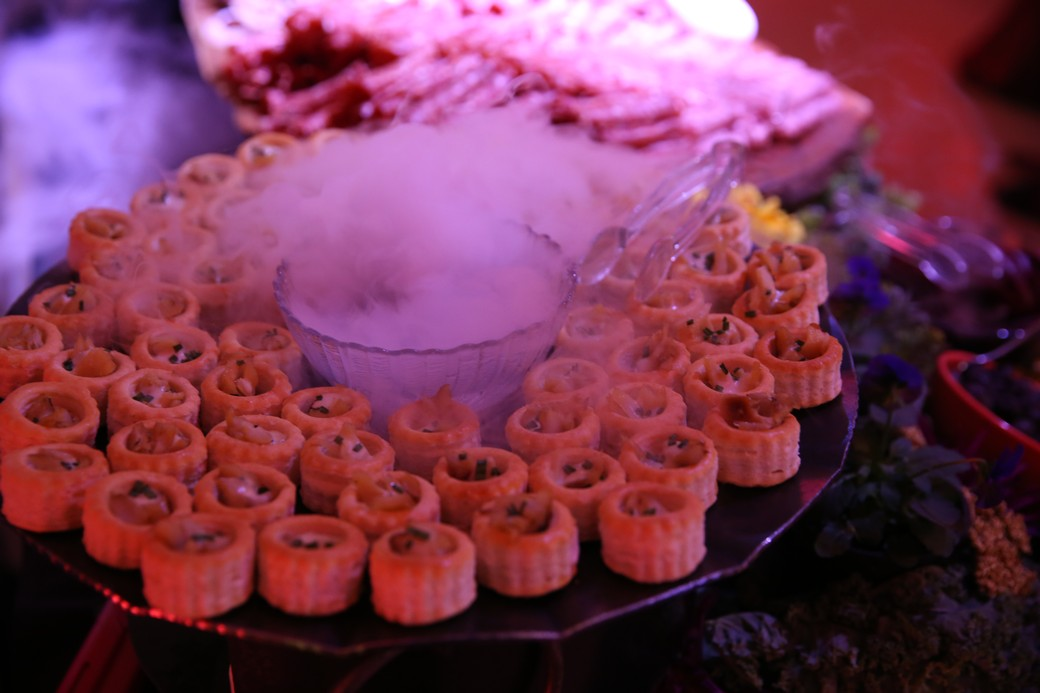Tray of appetizers surrounded by swirling dry ice smoke