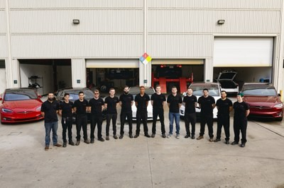 Automotive technician students posing in semi-circle outside of garage bay