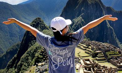 Female student with arms spread above Machu Picchu