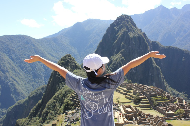 Young woman standing with arms open on Machu Picchu in Peru