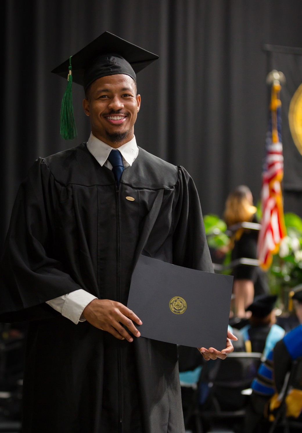 Graduate in cap and gown holding diploma